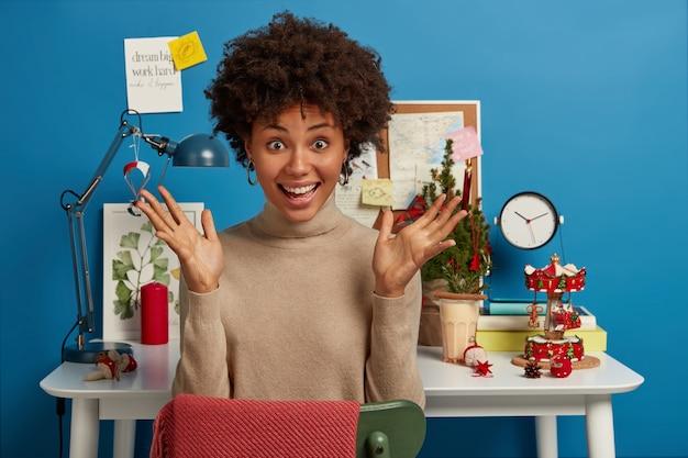 Радостная жизнерадостная смуглая женщина с поднятыми ладонями сидит за столом с елкой и другими праздничными атрибутами Бесплатные Фотографии