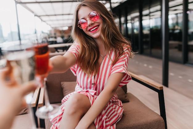 Радостная белая девушка в летнем платье проводит время в кафе. портрет чувственной блондинки в розовых очках, выражающей счастье в теплый день. Бесплатные Фотографии