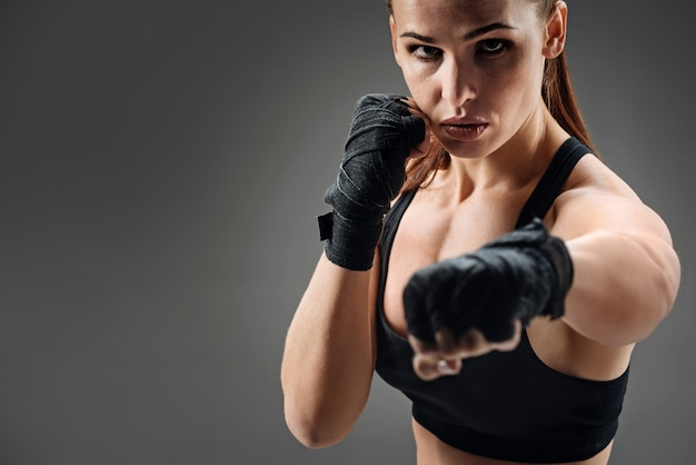 Joyful woman boxing on a grey Premium Photo