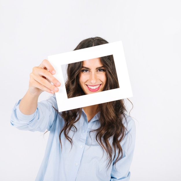 Joyful woman holding frame in front of face Photo | Free Download