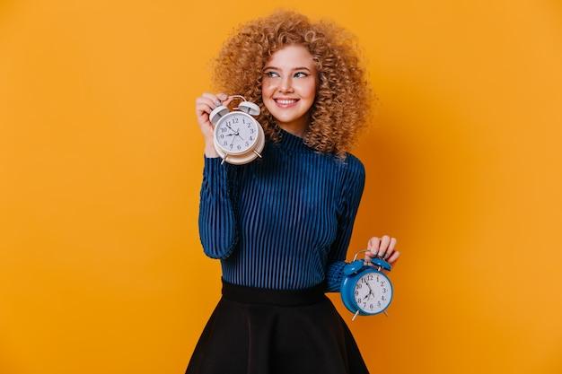 파란색 스웨터와 치마 노란색 공간에 큰 알람 시계와 함께 포즈에 즐거운 여자. 무료 사진