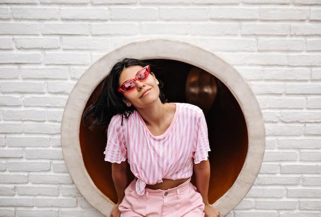 벽돌로 벽에 앉아 T- 셔츠에 즐거운 여자. 유행 선글라스에 매력적인 여자의 야외 촬영. 무료 사진