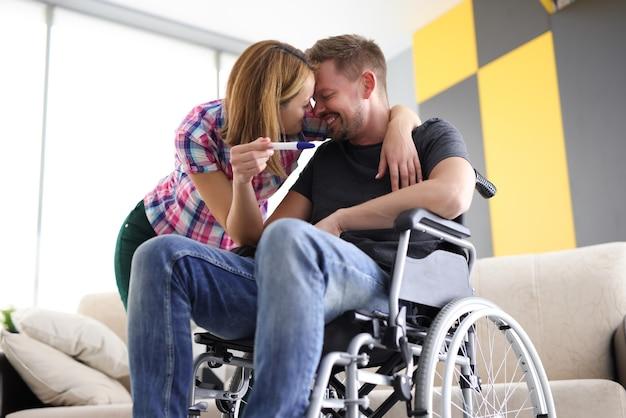 Joyful woman and man in wheelchair with pregnancy test Premium Photo