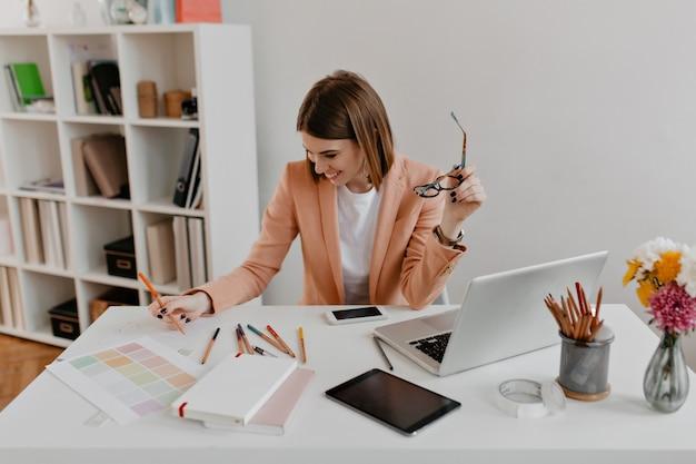 Donna allegra in giacca color pesca con il sorriso esamina i documenti mentre è seduto nel suo comodo ufficio luminoso. Foto Gratuite