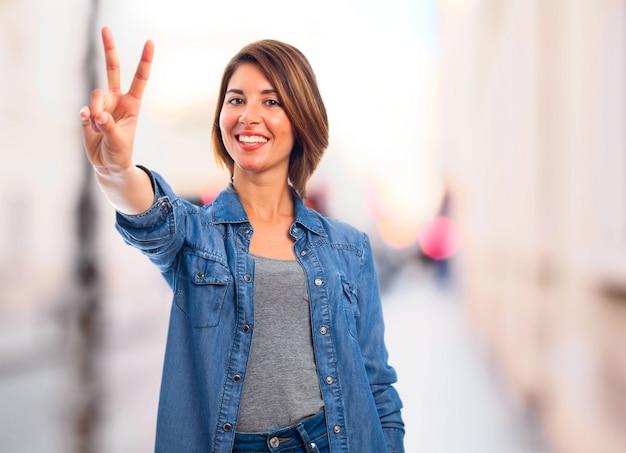 Joyful woman showing victory gesture Free Photo