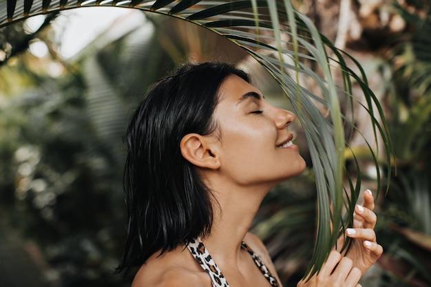 目を閉じてヤシの木を嗅ぐうれしそうな女性。休暇を楽しんでいる美しい日焼けした女性の屋外ショット。 無料写真