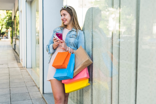 Joyful woman standing with shopping bags, smartphone and credit card Free Photo