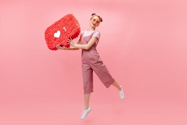 Joyful woman in stylish jumpsuit jumping on pink background, holding like sign. Free Photo
