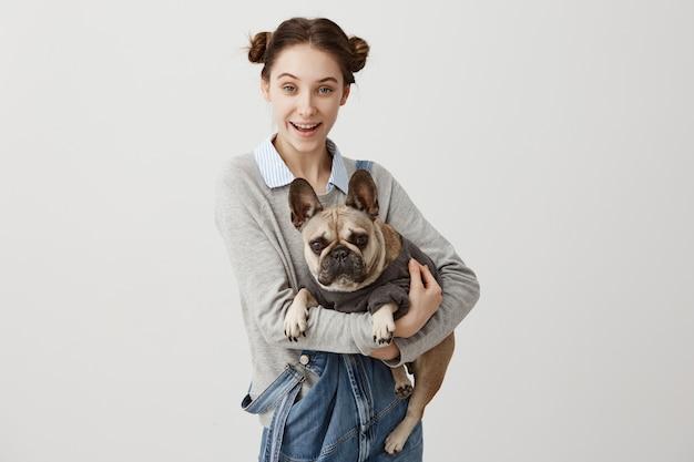 Радостная женщина с двойными булочками держит французского бульдога в руках, чувствуя заботу и ответственность. большие друзья человек и собака с удовольствием играют вместе дома. концепция дружбы Бесплатные Фотографии