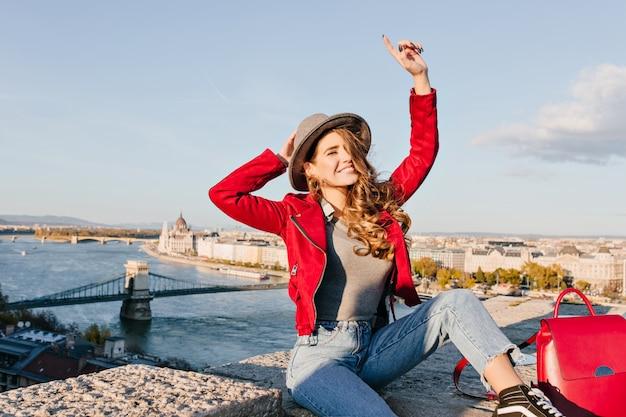 街の背景にポーズをとっている間、明るい茶色の髪の幸せな手を振ってうれしそうな女性 無料写真