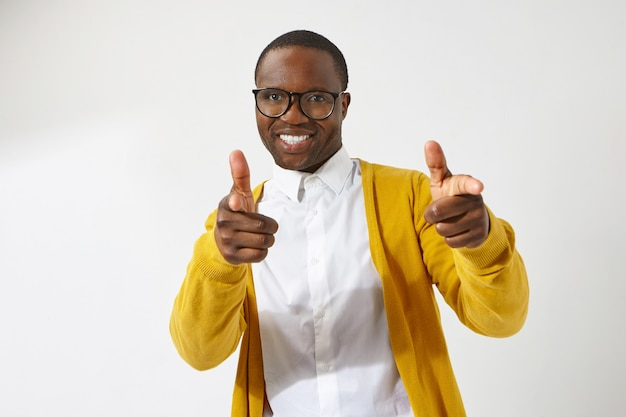 Joyful young afro american male hipster wearing stylish eyeglasses and cardigan smiling broadly, pointing index fingers , having positive friendly facial expression Free Photo