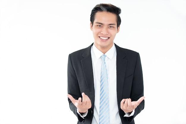 Joyful young asian businessman gesturing Free Photo
