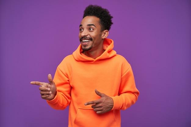 うれしそうな若いひげを生やした暗い肌の巻き毛のブルネットの男性は、人差し指を上げて、紫色のオレンジ色のパーカーを着て、広い陽気な笑顔で脇を見てください 無料写真