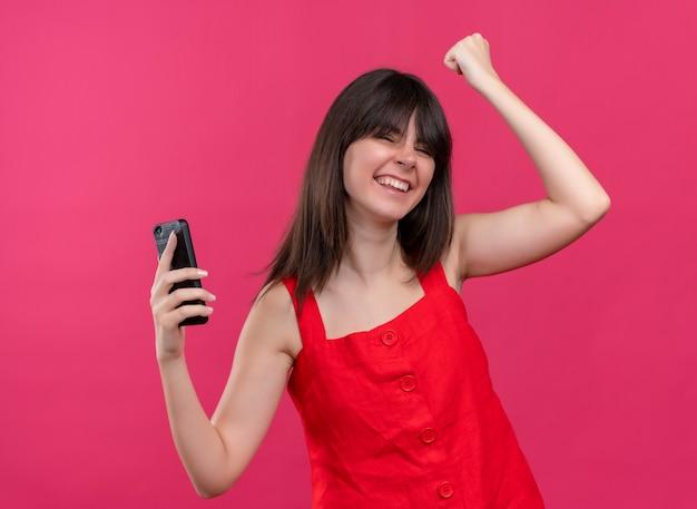 電話を保持し、孤立したピンクの背景に目を閉じて拳を上げるうれしそうな若い白人の女の子 無料写真