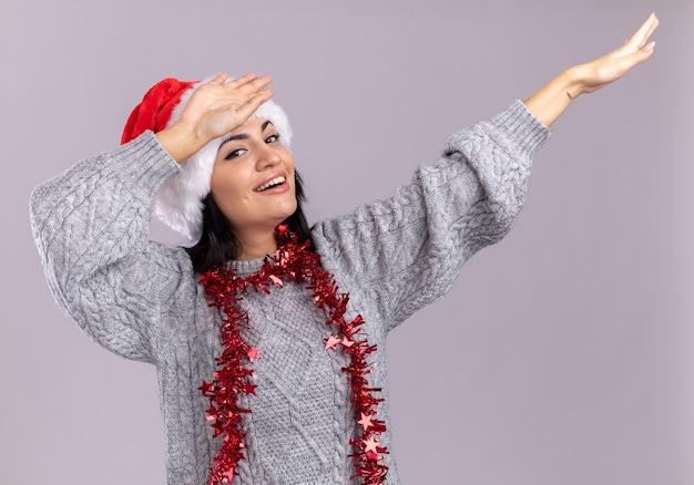 クリスマスの帽子と白い壁に分離された軽くたたくジェスチャーをしている首の周りに見掛け倒しの花輪を身に着けているうれしそうな若い白人の女の子 無料写真