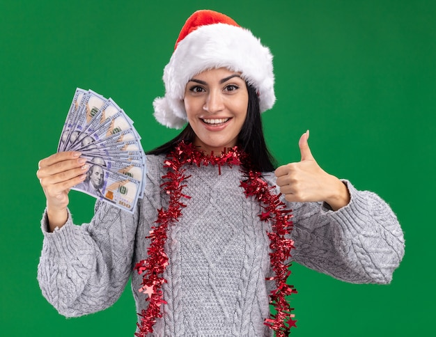 Joyful young caucasian girl wearing christmas hat and tinsel garland around neck holding money  showing thumb up isolated on green wall Free Photo