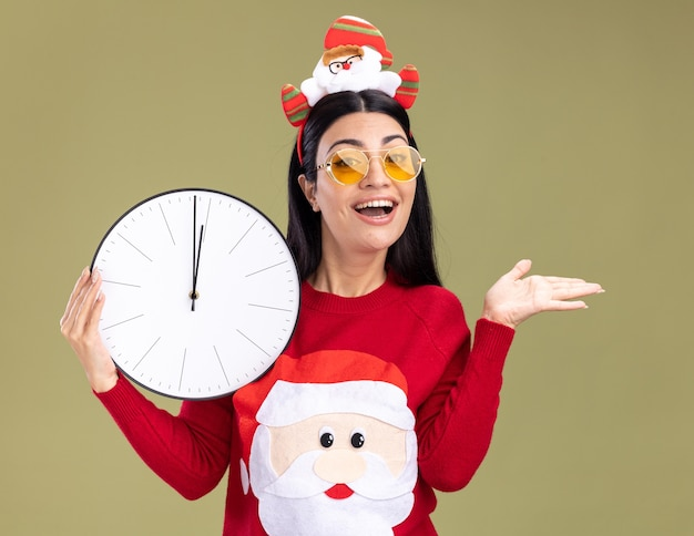 Gioiosa giovane ragazza caucasica che indossa la fascia di babbo natale e maglione con gli occhiali che tengono l'orologio che mostra la mano vuota isolata sulla parete verde oliva Foto Gratuite