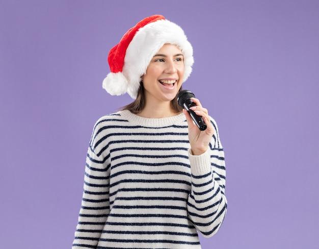 サンタの帽子をかぶったうれしそうな若い白人の女の子は、側を見てマイクを保持します 無料写真