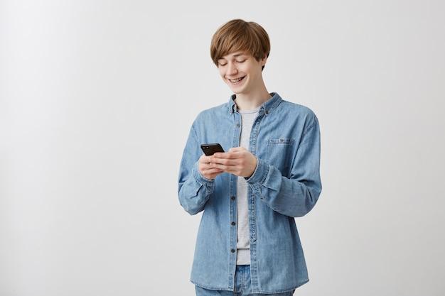 Радостный молодой кавказский хипстер со светлыми волосами, одетый в джинсовую рубашку поверх серой футболки, играет в видеоигру с включенным электронным гаджетом. счастливый улыбающийся парень, серфинг в интернете с помощью wi-fi на мобильный телефон Бесплатные Фотографии