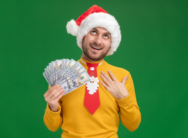Joyful young caucasian man wearing christmas hat and tie holding money putting hand on chest looking up isolated on green wall with copy space Free Photo