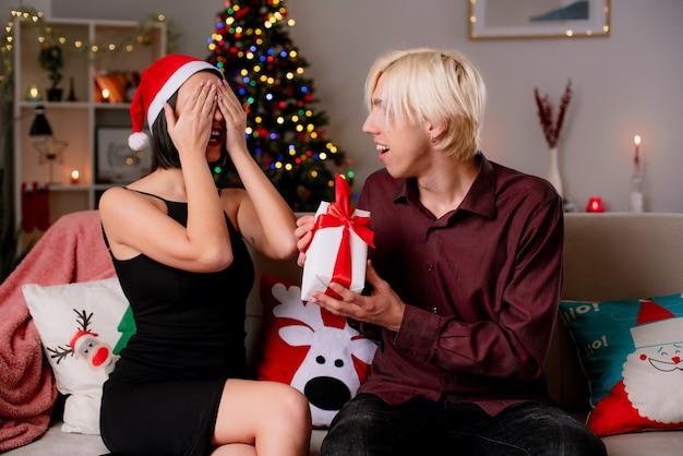 Gioiosa giovane coppia a casa nel periodo natalizio con indosso il cappello della santa e ricevere regali Foto Gratuite