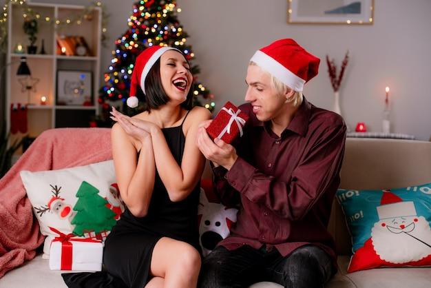Gioiosa giovane coppia a casa nel periodo natalizio indossando il cappello della santa seduto sul divano in soggiorno che riceve i regali Foto Gratuite