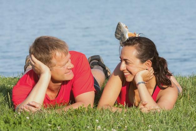 ハンガリーのバラトン湖の岸にうれしそうな若いカップルが重なっています。 Premium写真