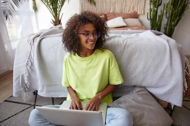 Joyful young dark skinned woman with glasses leaning on bed in sleeping room, working from home with laptop, keeping hands on keybord, being in nice mood Free Photo
