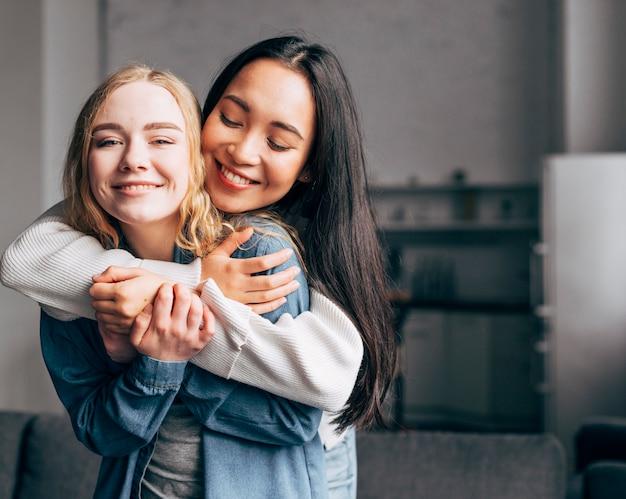 Joyful young girlfriends cuddling at home Free Photo