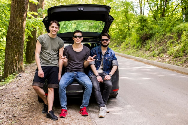 Joyful young guys sitting in trunk on forest road Free Photo