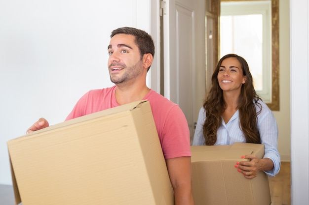 판지 상자와 함께 그들의 새 아파트에 오는 즐거운 젊은 라틴 부부 무료 사진