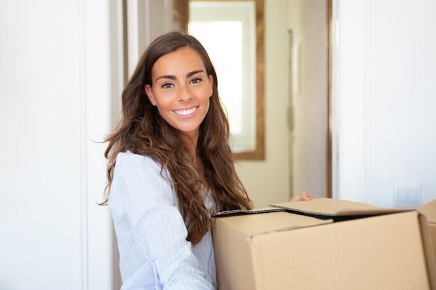 새 아파트로 이동하는 즐거운 젊은 라틴 여자, 들고 판지 상자를 들고, 무료 사진