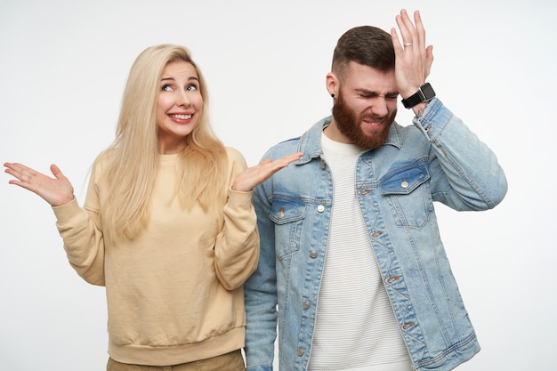 Joyful young long haired blonde woman raising confusedly palms and smiling widely while posing on white with bewildered brunette handsome male in jeans coat Free Photo