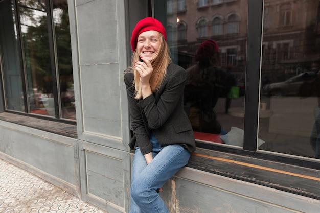 窓辺の上に屋外に座って、エレガントな服を着て、楽しく笑いながら彼女の顔に手を上げてうれしそうな若い素敵なブロンドの長い髪の女性 無料写真