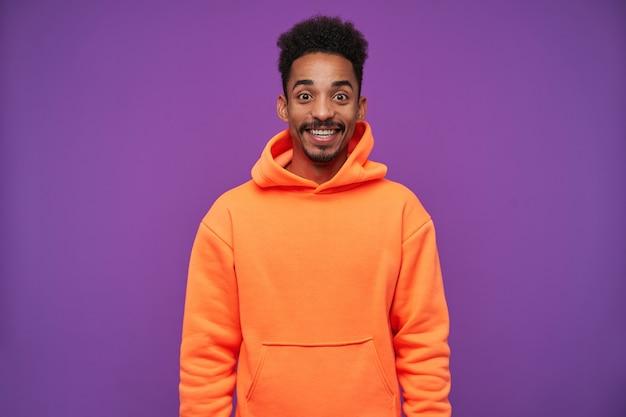スポーティーな服装で紫の上に立っている間、驚くほどに見え、広く笑っているひげを持つうれしそうな若い素敵な茶色の目の暗い肌のブルネットの男性 無料写真
