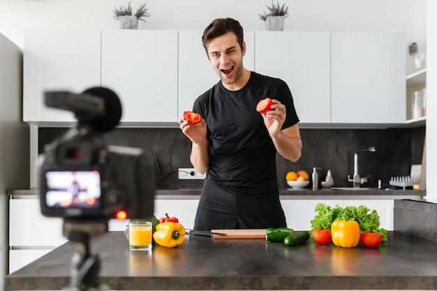Joyful young man filming his video blog episode Free Photo