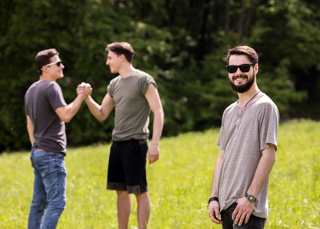 Joyful young man standing on picnic with friends Free Photo