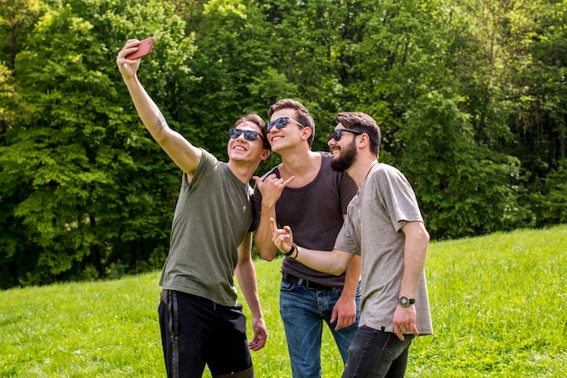 Giovani allegri che prendono selfie in natura Foto Gratuite