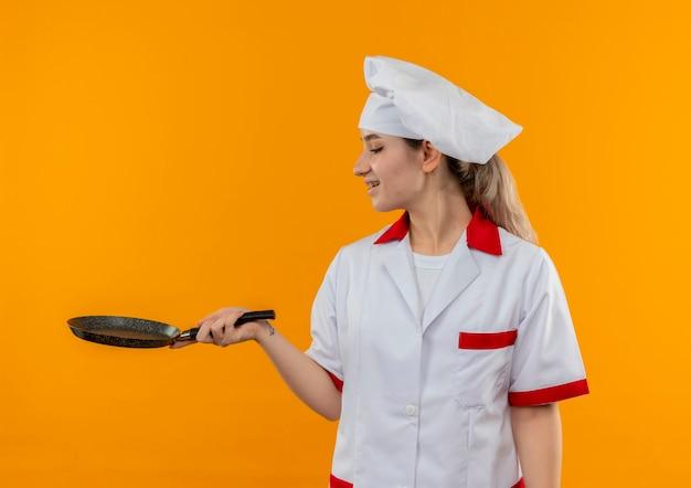 Gioioso giovane cuoco grazioso in uniforme da chef con parentesi graffe dentali che tiene e guardando la padella isolata su uno spazio arancione Foto Gratuite