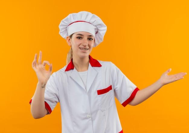 シェフの制服を着たうれしそうな若いかわいい料理人。歯列矯正器でokサインをし、オレンジ色のスペースで孤立した空の手を見せています。 無料写真