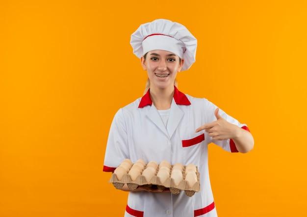 オレンジ色のスペースで隔離された卵のカートンを保持し、指している歯科用ブレースを備えたシェフの制服を着たうれしそうな若いかわいい料理人 無料写真