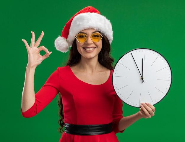 Gioiosa giovane bella ragazza che indossa il cappello della santa e bicchieri tenendo l'orologio guardando la telecamera facendo segno ok isolato su sfondo verde Foto Gratuite