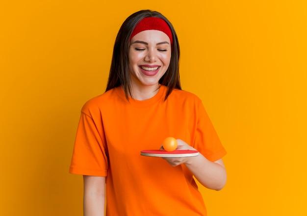 머리띠와 팔찌를 착용하고 그것에 공을 탁구 라켓을보고 즐거운 젊은 스포티 한 여자 무료 사진