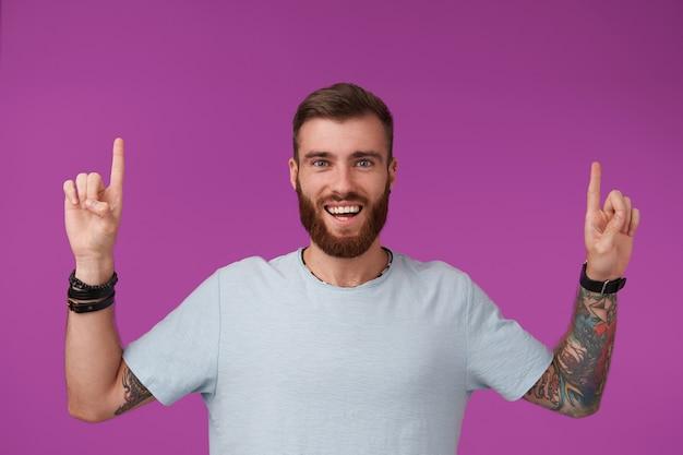 넓은 행복한 미소로 보라색에 서서 검지 손가락을 올리는 동안 파란색 티셔츠를 입고 짧은 머리를 가진 즐거운 젊은 면도하지 않은 문신을 한 남자 무료 사진