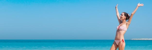 Радостная молодая женщина в купальнике с поднятыми руками у стены моря Premium Фотографии