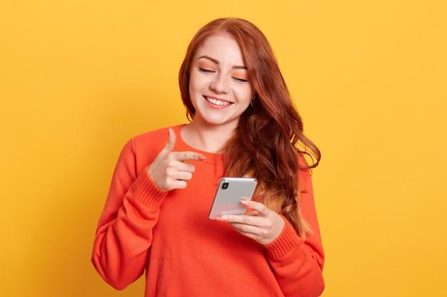 스마트 폰 화면을 손에 가리키는 즐거운 젊은 여자 프리미엄 사진