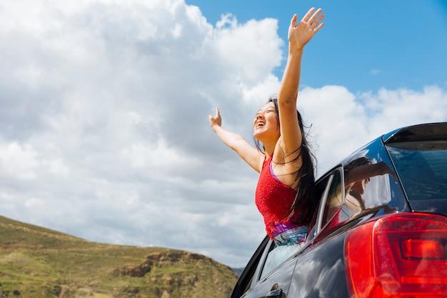 Joyful young woman raising hands to sky Free Photo