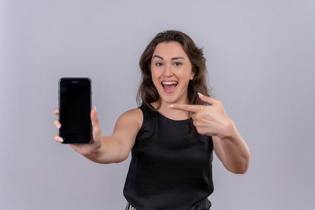 Gioiosa giovane donna che indossa la maglietta nera ha tenuto il telefono per inoltrare e indicare il telefono sul muro bianco Foto Gratuite