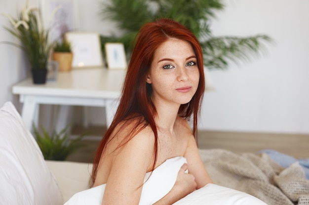 Joyful young woman with ginger hair, freckles and nude shoulders sitting on bed, wrapped in blanket, feeling happy, awakened in hotel room on first day of honeymoon, smiling charmingly Free Photo