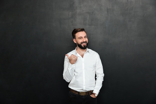 Joyous adult guy in office posing on camera, gesturing with thumb aside over dark gray copy space Free Photo